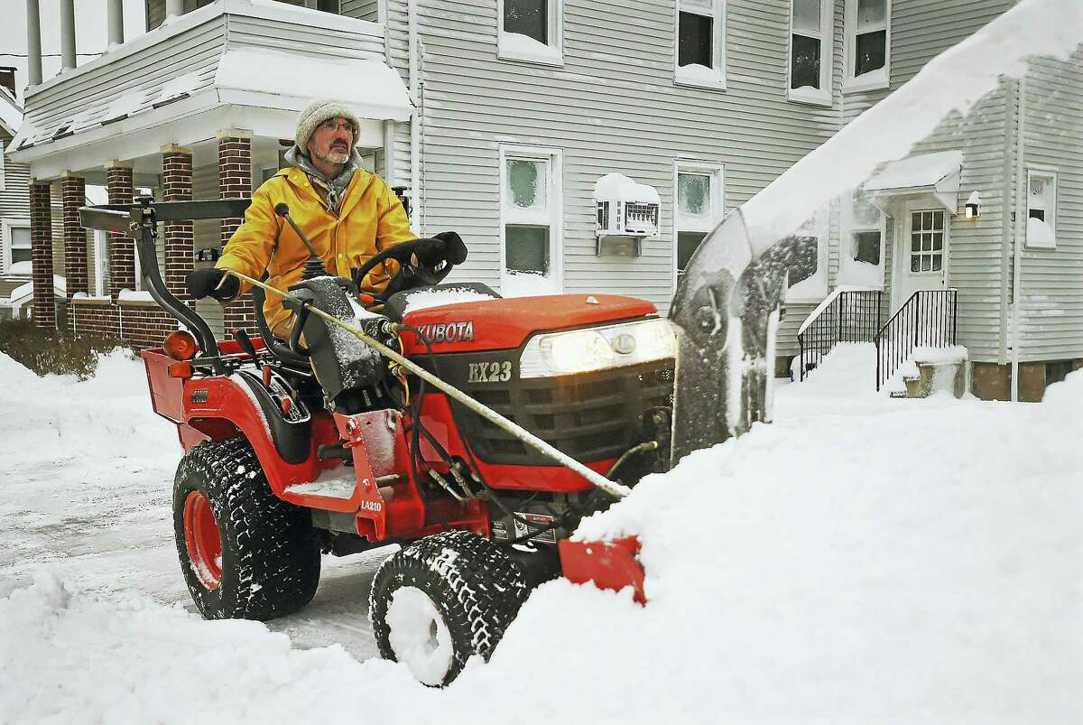 Ed Amato aboard his Kubota RX23 to plow the sidewalk on Pearl Street in Middletown on Thursday.