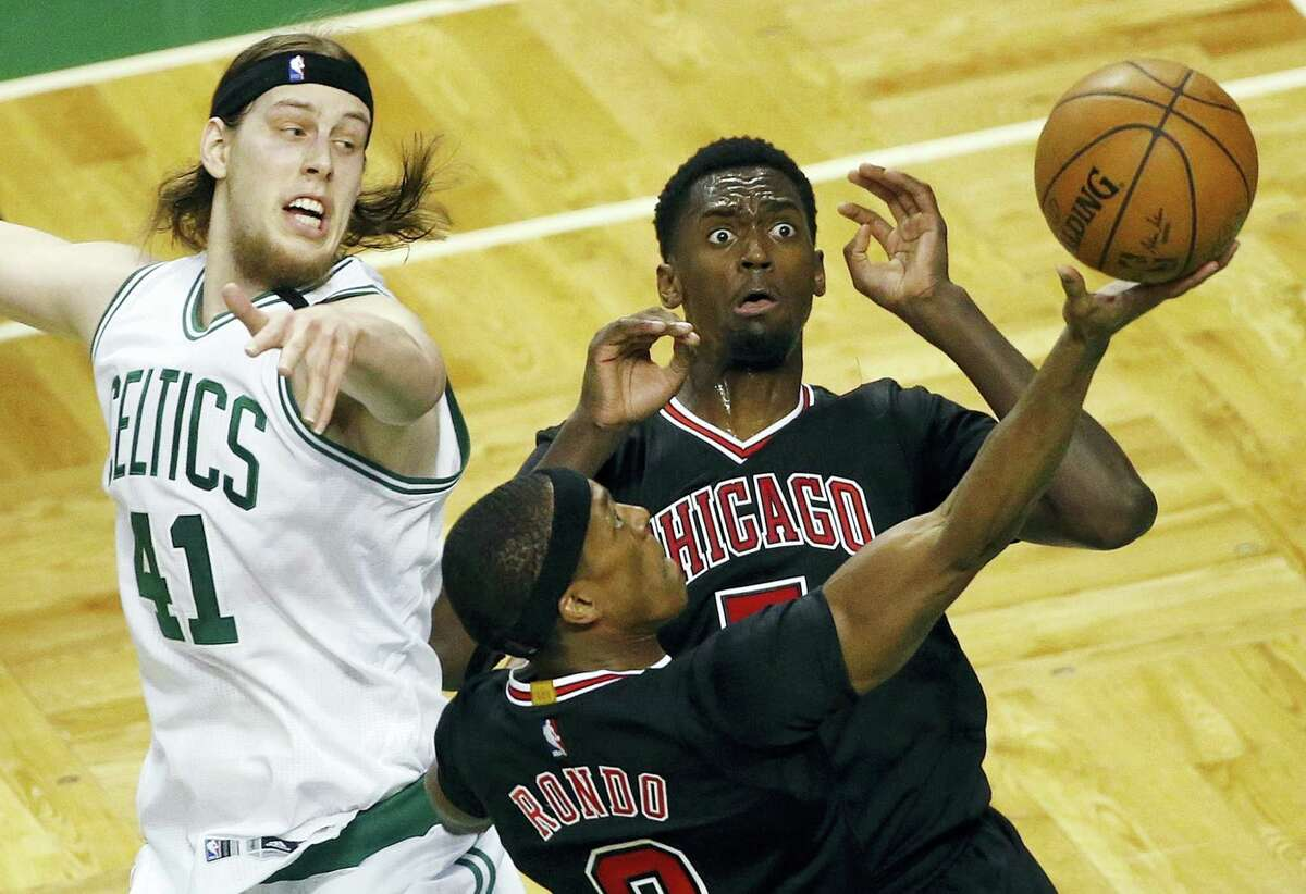 The Bulls' Rajon Rondo (9) goes up to shoot in front of teammate Bobby Portis and the Celtics' Kelly Olynyk during the second quarter Sunday in Boston.