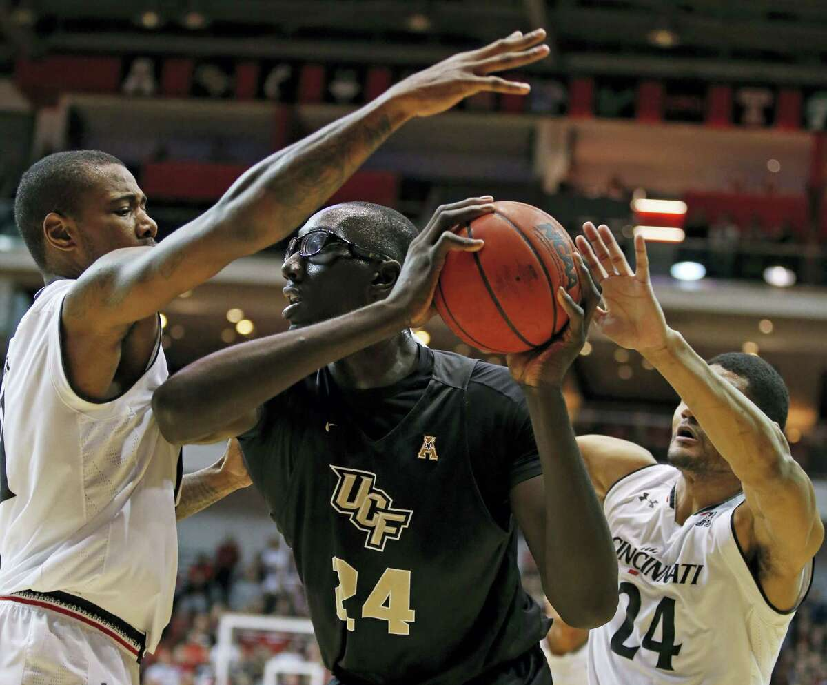 Central Florida center Tacko Fall, center, is pressured by Cincinnati's Gary Clark, left, and Kyle Washington during a recent game.