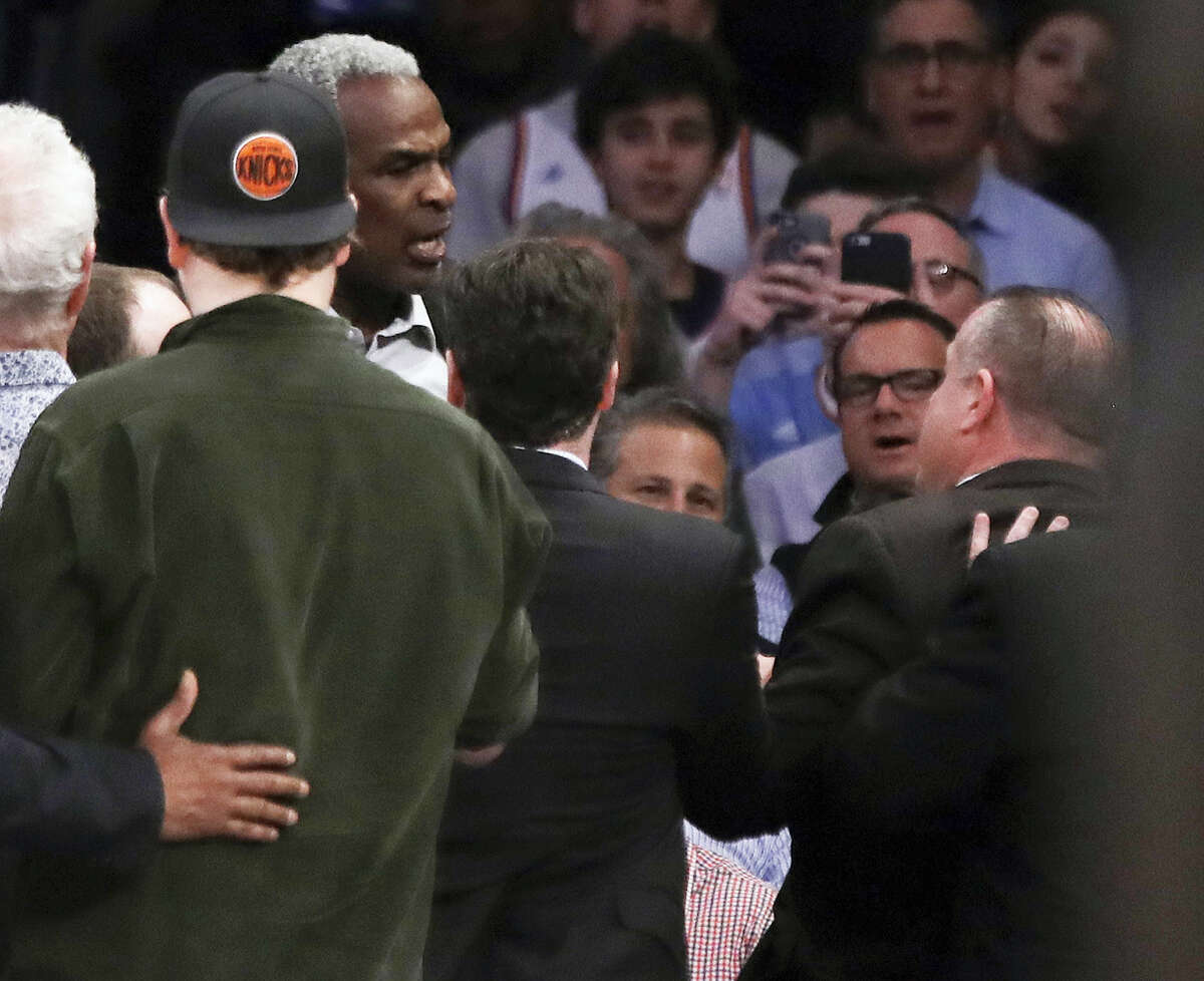 Former New York Knicks player Charles Oakley exchanges words with a security guard.