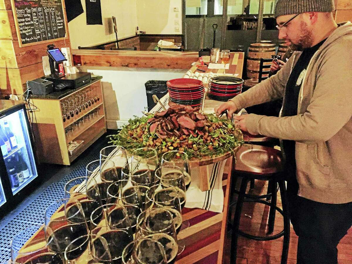 Co-owner Craig Sklar puts out food during a seminar at The Beer Collective recently. Courses are held about twice a month at the craft beer bar and restaurant in New Haven.