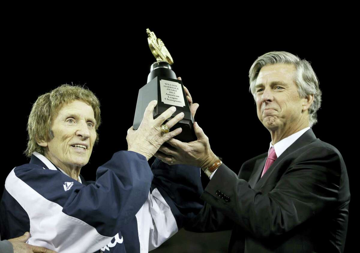 Tigers owner Mike Ilitch, left, and then general manager Dave Dombrowski, lift the William Harridge Trophy after their team won the ALCS in 2012.
