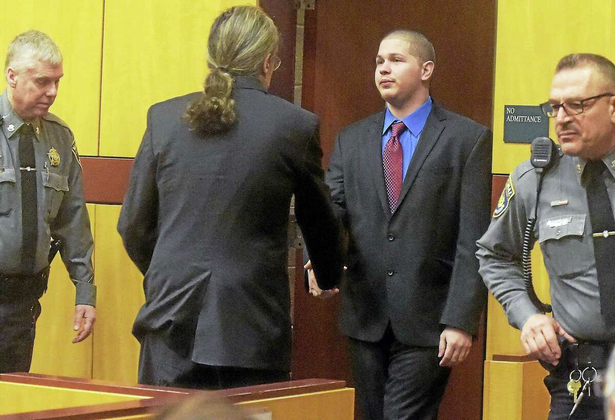 PATRICK RAYCRAFT — Hartford Courant/Pool Tony Moreno, shown entering the courtroom at the start of his murder trial on Friday morning, shakes hands with his attorney Norm Pattis.