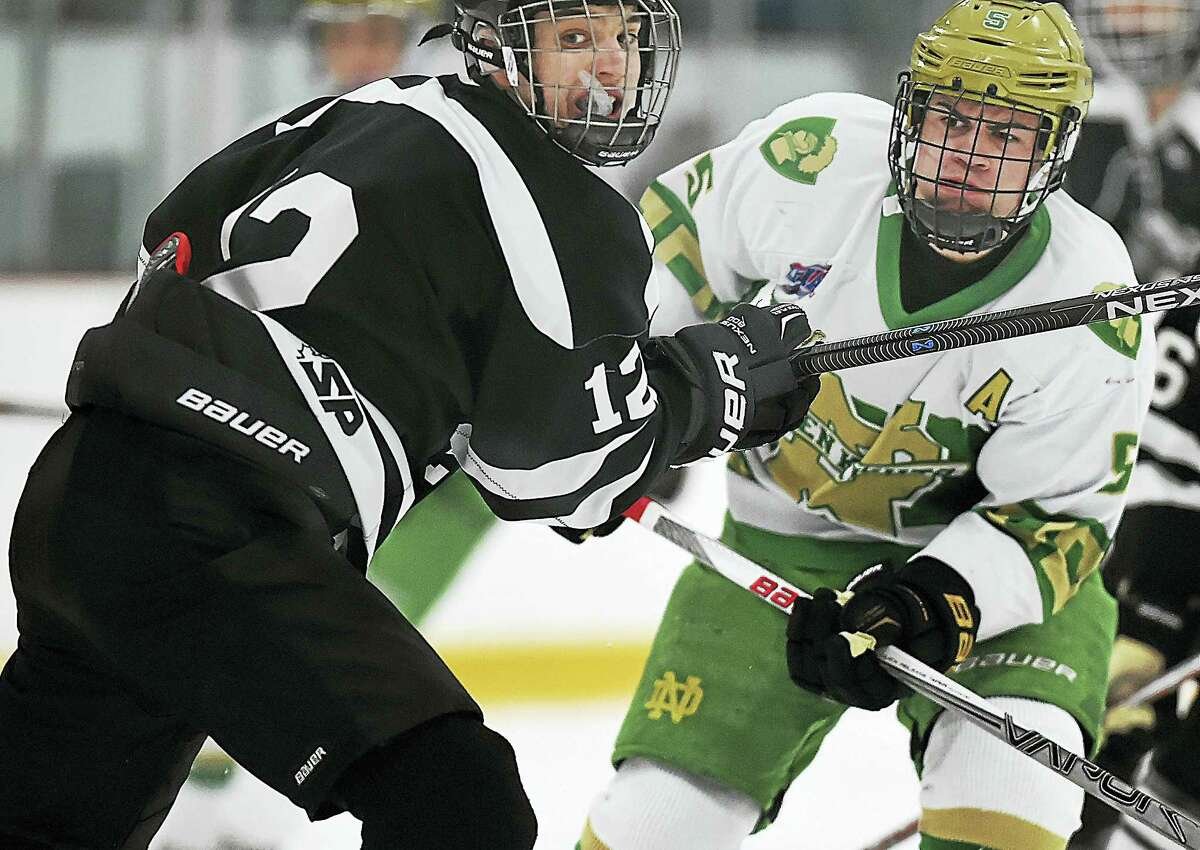 Xavier sophomore defenseman follows the puck to the goal as Notre Dame-West Haven senior forward Matthew Muro scores the first goal of the game. Xavier would battle back for a 3-3 tie at Bennett Rink in West Haven Wednesday.