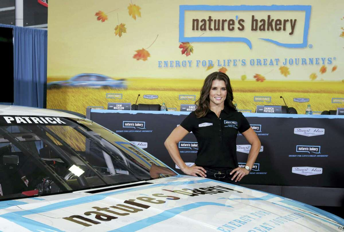 Danica Patrick poses by her new race car during a news conference.