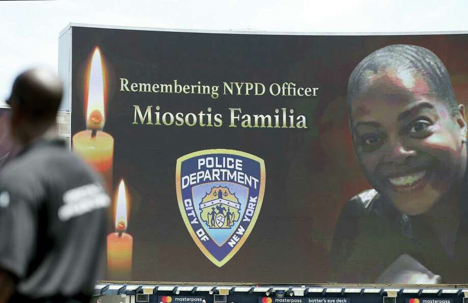 "A security guard stands at attention as New York Police Department officer Miosotis Familia is memorialized before the start of a baseball game between the New York Yankees and the Toronto Blue Jays in New York July 5. Familia was killed in an ""unprovoked attack,"" in the Bronx borough of New York, according to the NYPD Commissioner. Photo: AP Photo — Kathy Willens   / Copyright 2017 The Associated Press. All rights reserved."