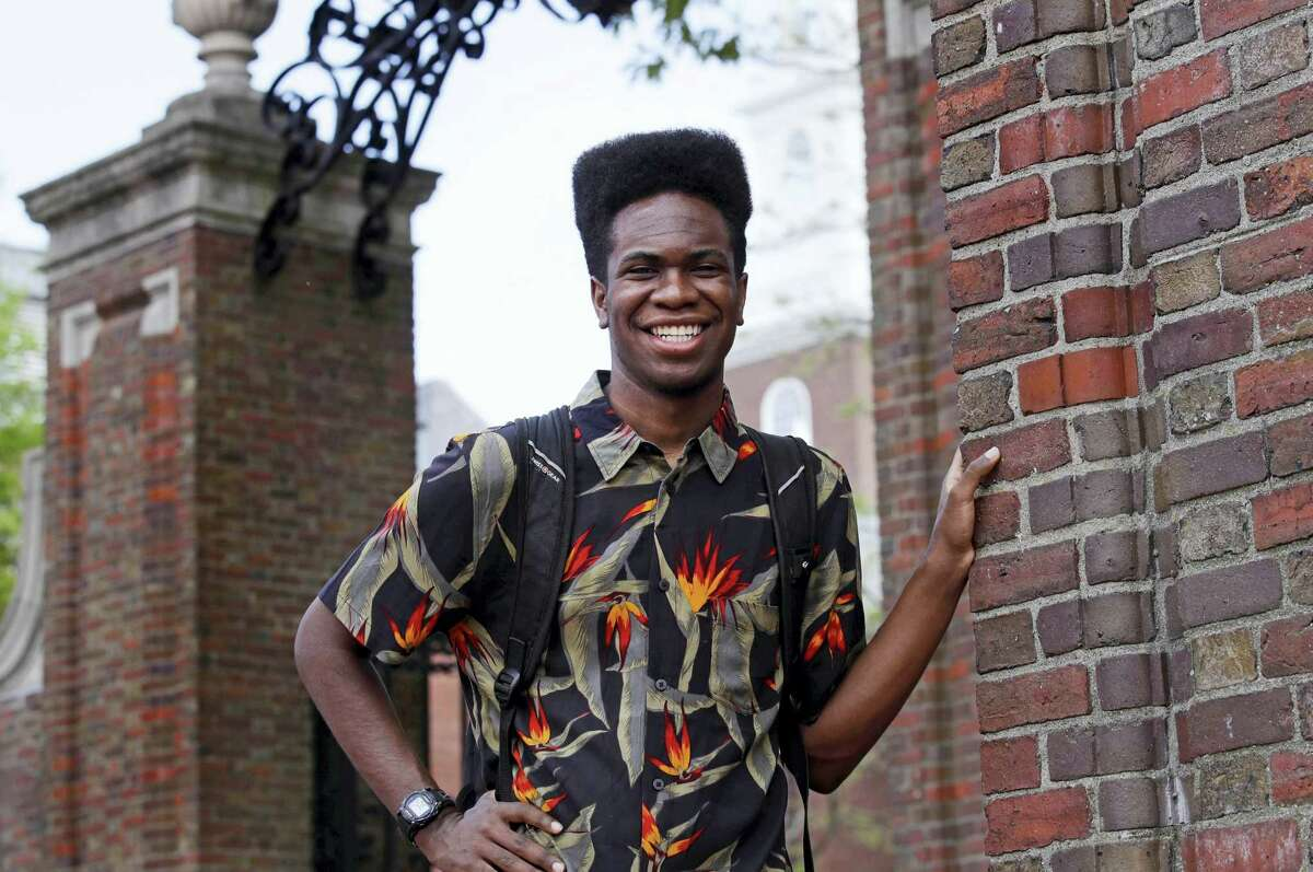 """Obasi Shaw poses outside the gates of Harvard Yard in Cambridge, Mass., Thursday, May 18, 2017. Shaw, an English major who graduates from Harvard next week, is the university's first student to submit his final thesis in the form of a rap album. The record, called """"Liminal Minds,"""" has earned the equivalent of an A- grade, good enough to ensure that Shaw will graduate with honors at the university's commencement next week."""