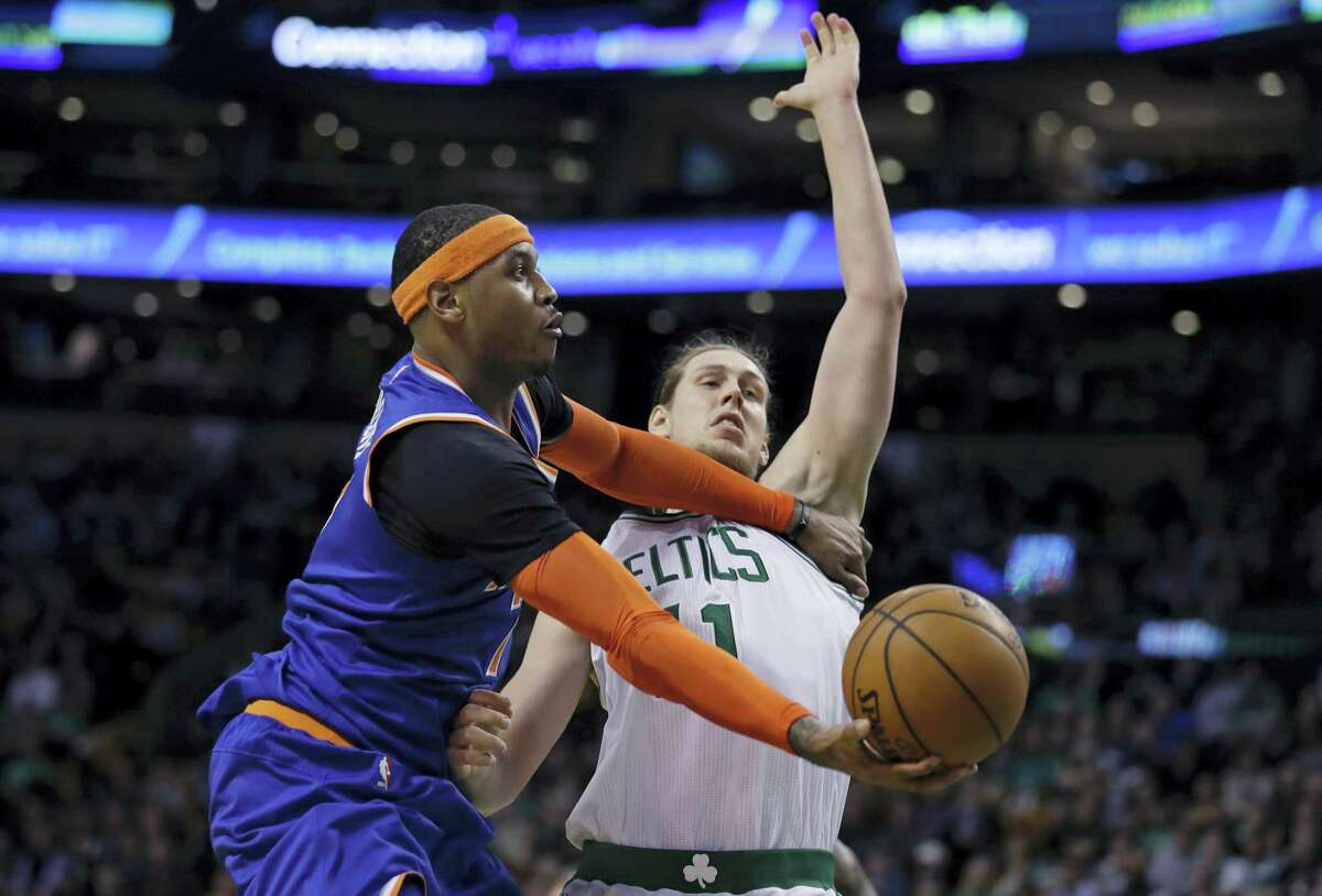 New York Knicks forward Carmelo Anthony, left, holds back Boston Celtics center Kelly Olynyk as he drives to the basket during the second half in Boston, Wednesday The Knicks defeated the Celtics 117-106.