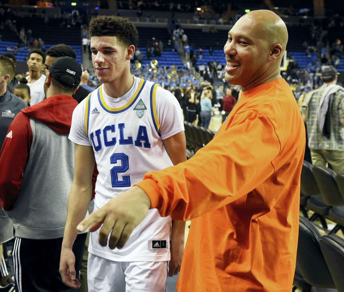 In this Nov. 20, 2016 photo, UCLA's Lonzo Ball (2) walks by his father LaVar Ball, right, to greet family members after UCLA defeated Long Beach State in an NCAA college basketball game in Los Angeles. By now the entire basketball world knows Lonzo Ball is a singular talent with a unique parent.