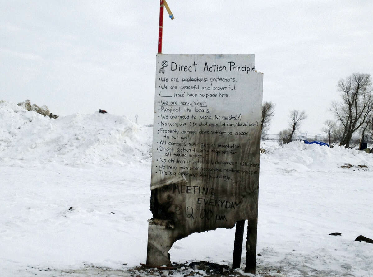 A sign is seen at an encampment set up near Cannon Ball, N.D., Feb. 8, for opponents against the construction of the Dakota Access pipeline. Opponents called for protests around the world as the Army prepared to green-light the final stage of the $3.8 billion project's construction. The Army said Feb. 7, that it will allow the four-state pipeline to cross under a Missouri River reservoir in North Dakota, the last big chunk of construction.