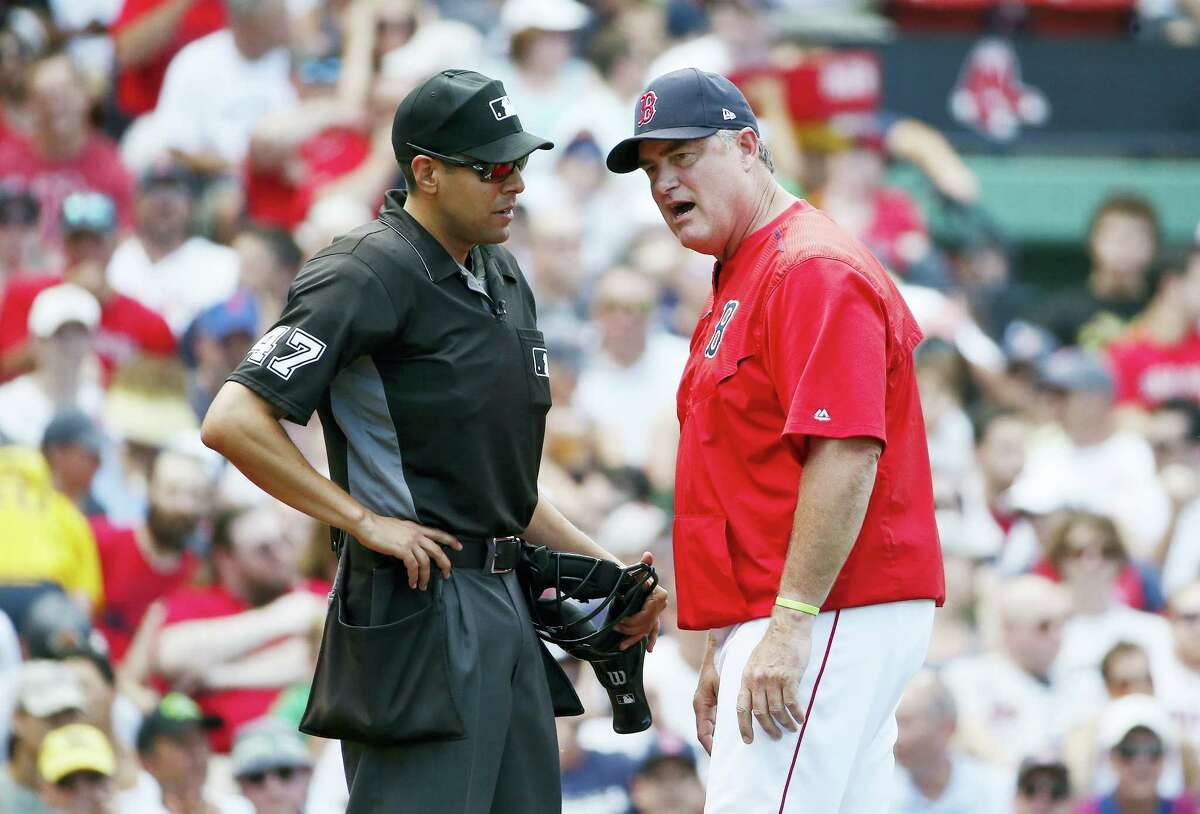 Boston Red Sox manager John Farrell argues with home plate umpire Gabe Morales during the fourth inning of the first game of a baseball doubleheader in Boston on July 16, 2017.