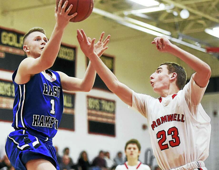 East Hampton's Nic Distefano elevates in the paint against Cromwell defender David Dewey on Tuesday night at Salafia Gymnasium. Photo: Catherine Avalone - New Haven Register  / Catherine Avalone/New Haven Register