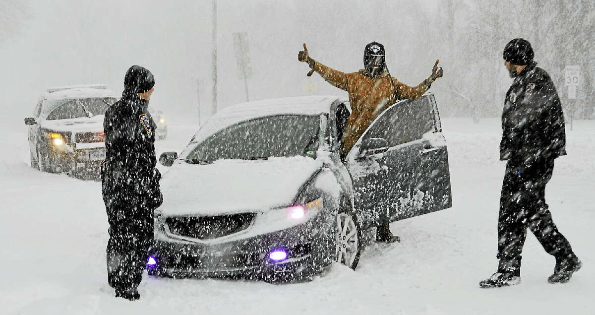 Mid-morning Thursday, as heavy snow continued to fall, several Middletown police officers helped a man whose car had gotten stuck in a drift on St. John Square.