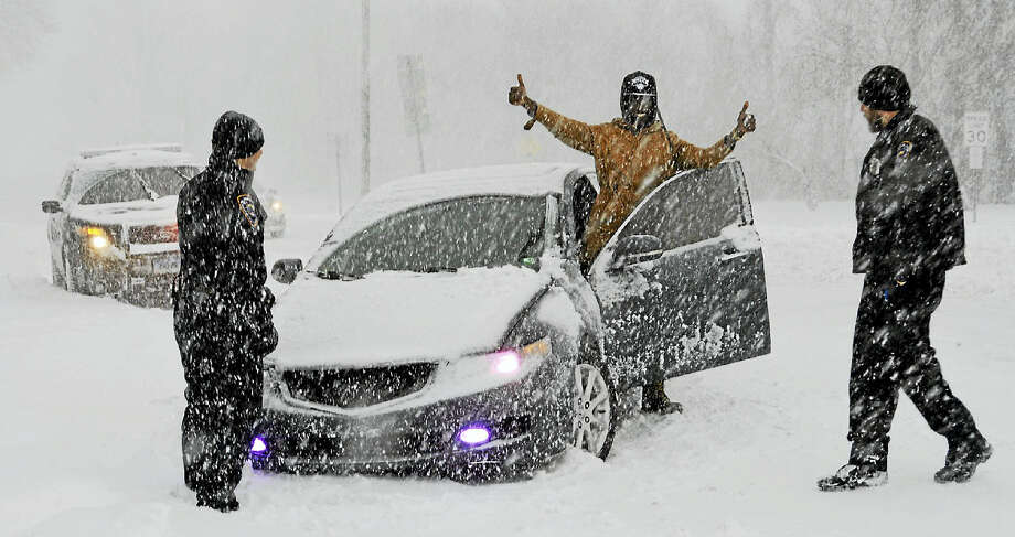 Mid-morning Thursday, as heavy snow continued to fall, several Middletown police officers helped a man whose car had gotten stuck in a drift on St. John Square. Photo: Cassandra Day — The Middletown Press