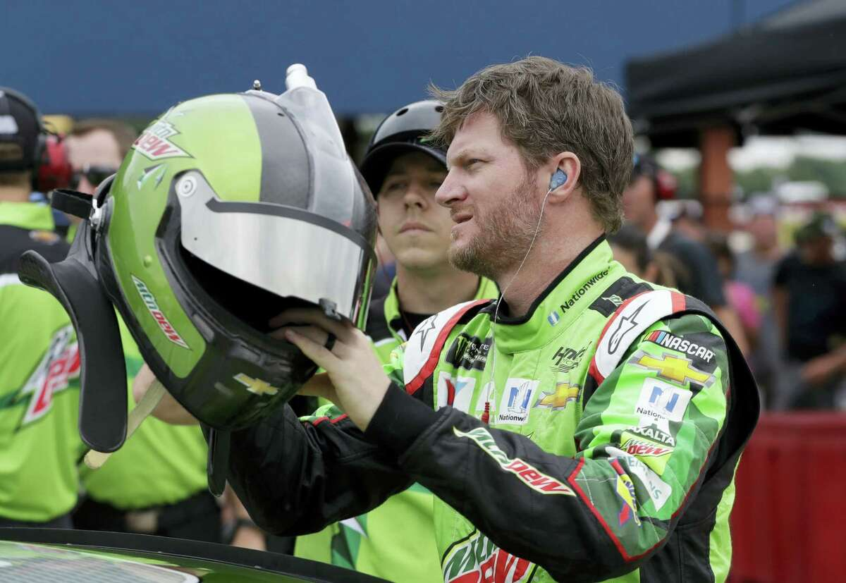 Dale Earnhardt Jr., reaches for his helmet before qualifying Friday in Brooklyn, Mich. With Earnhardt retiring after this season, his seat in the No. 88 Chevrolet is the biggest prize of free agency for drivers.