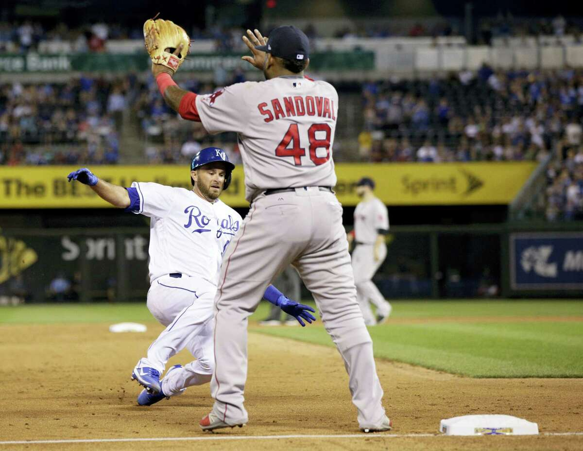 The Royals Drew Butera, left, slides into third base with a triple as Pablo Sandoval waits for the throw in the seventh inning on Monday.