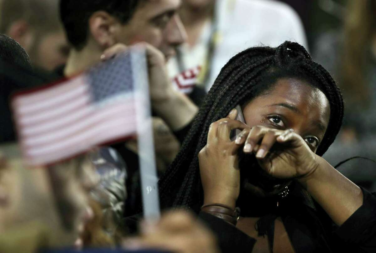 A woman weeps as election results are reported during Democratic presidential nominee Hillary Clinton's election night rally in the Jacob Javits Center glass enclosed lobby in New York. As Donald Trump approaches his inauguration as president, young Americans have a deeply pessimistic view about his incoming administration, with young blacks, Latinos and Asian Americans particularly concerned about what's to come in the next four years.