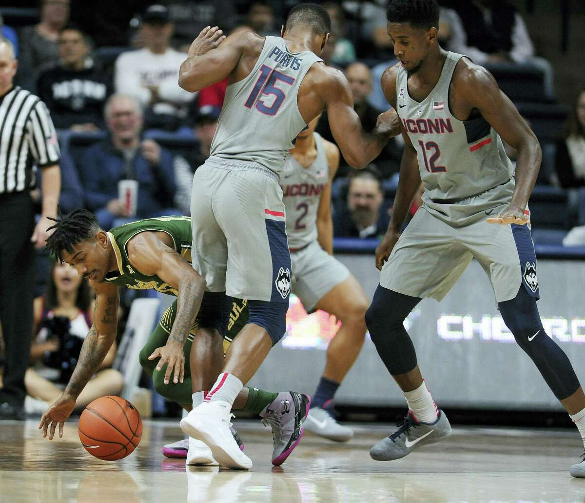 South Florida's Geno Thorpe stumbles between Connecticut's Rodney Purvis (15) and Kentan Facey (12) during the first half Wednesday in Storrs.