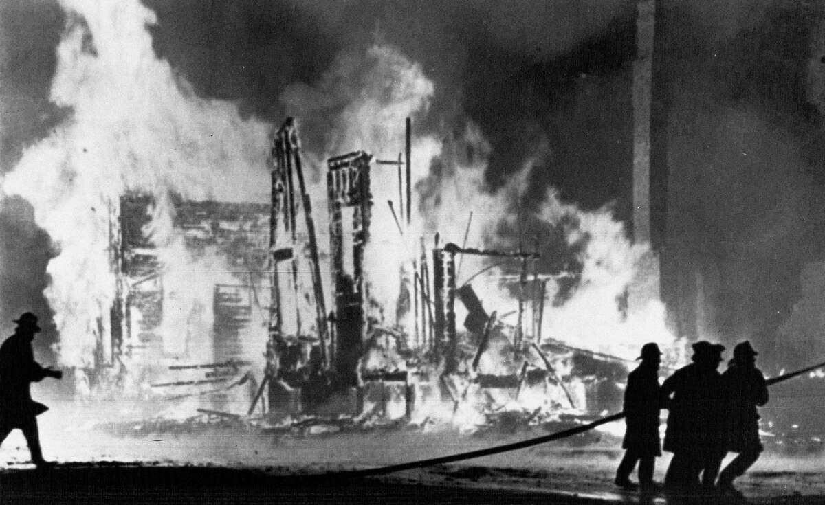 FILE - In this July 25, 1967 file photo, firefighters try to control blazing buildings after riots in Detroit. Hundreds of fires were reported in the city. Five days of violence would leave 33 blacks and 10 whites dead, and more than 1,400 buildings burned. More than 7,000 people were arrested. (AP Photo/File)