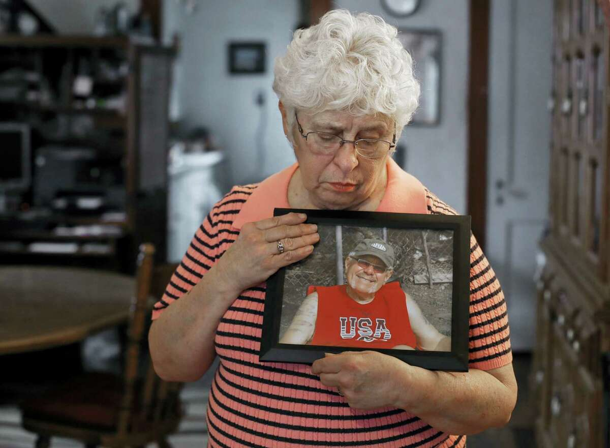 In this Thursday, Jan. 26, 2017, photo, Kay Taynor holds a photo of her late husband, Gary, in Toledo, Ohio. Dozens of patients from a now-closed memory loss clinic in Ohio say its director told them they had Alzheimer's disease when they really didn't. More than 50 people have sued, saying they thought for months they had the mind-robbing disease. Taynor was diagnosed with Alzheimer's on her second visit to clinic director Sherry-Ann Jenkins and then referred five or six friends and family members to her office, including her husband of 48 years. All were told they had the disease, she said, but her husband, Gary, took it hardest.