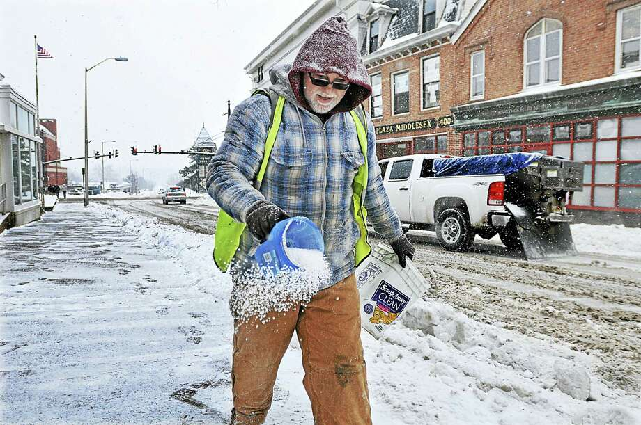 A man sprinkles salt on the sidewalk on College Street at Citizen Bank in Middletown in this archive photograph. Meteorologists are predicting the entire state will be blanketed by up to 10 inches of snow following a storm expected to begin late Wednesday and stretch into Thursday. Photo: File Photo  / TheMiddletownPress