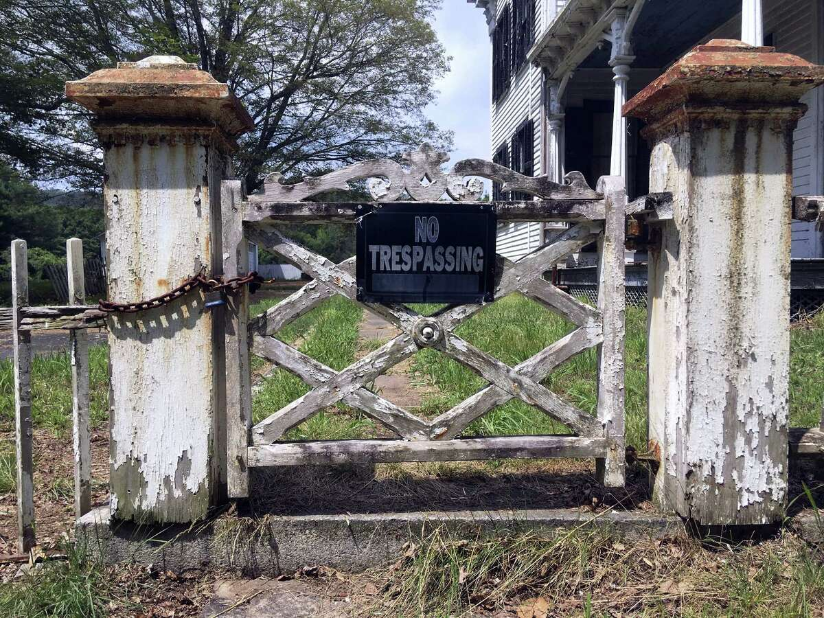 In this July 12 photo, a sign declares no trespassing allowed in an abandoned house on the grounds of a long-abandoned, 62-acre village in East Haddam.