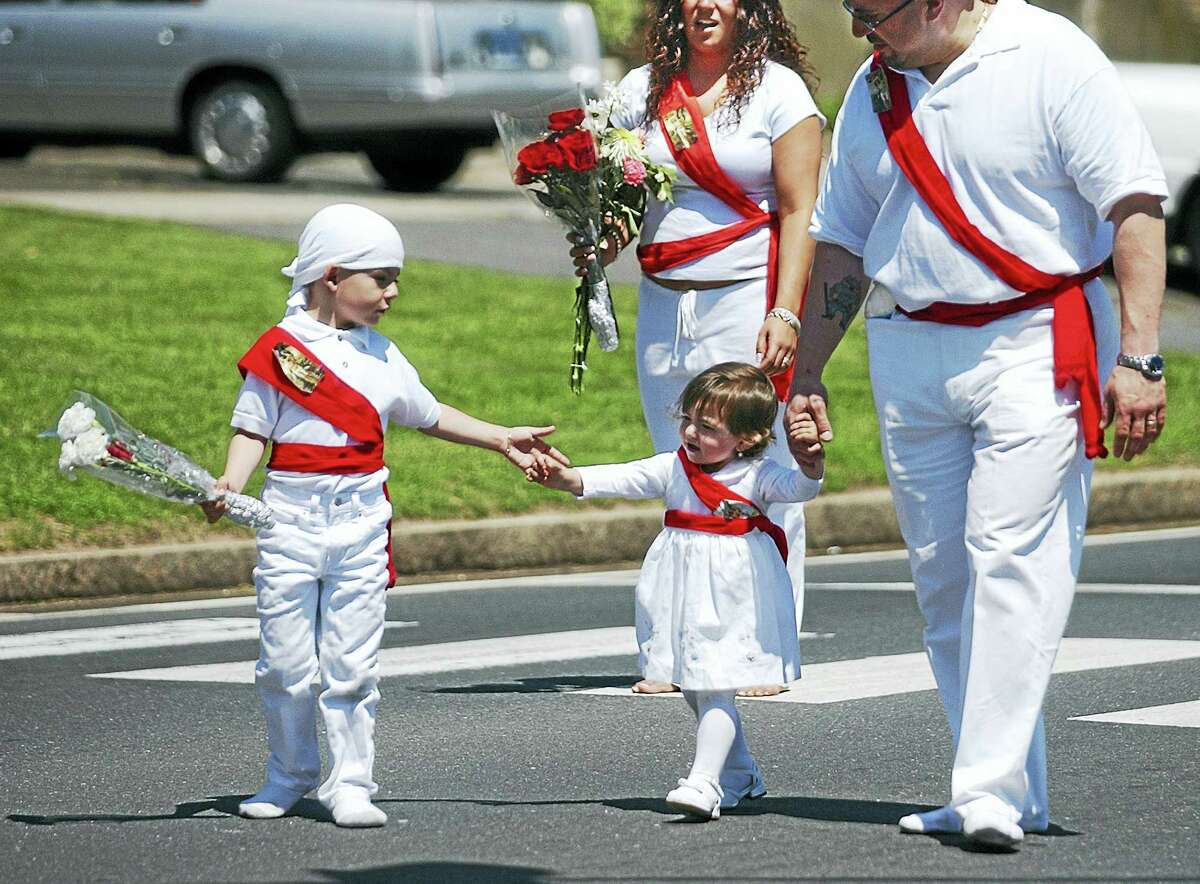 John Giuliano of Middletown, Thomas Way of Portland and Said Oruczadeh Jr. of Middletown, left to right, pray to St. Sebastian in Middletown during the celebration of the martyr's life and death at the St. Sebastian Feast.
