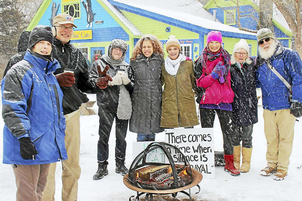 """""""There comes a time when silence is betrayal"""" says a sign near Together We Rise Building Bridges for Justice members warming up by a fire as snow falls at a recent vigil outside Two Wrasslin' Cats in East Haddam."""