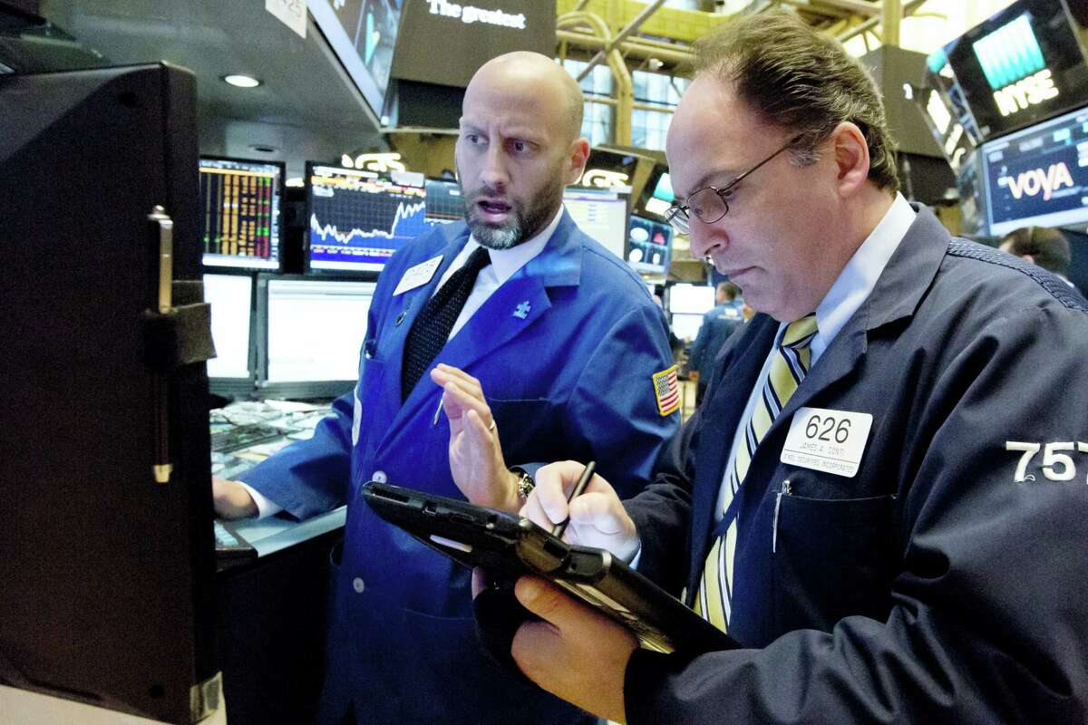Specialist Meric Greenbaum, left, and trader James Conti work on the floor of the New York Stock Exchange Wednesday.