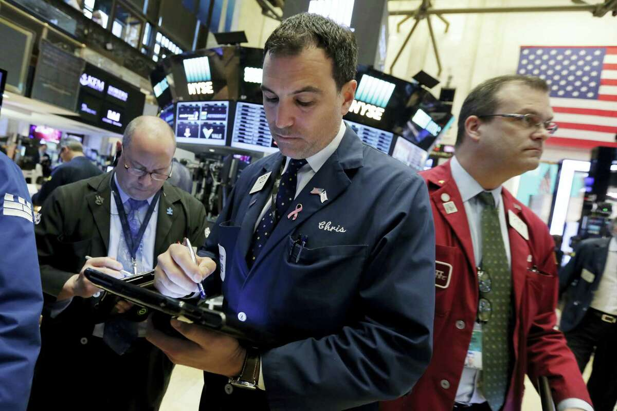Trader Christopher LaGana, center, works on the floor of the New York Stock Exchange Wednesday.