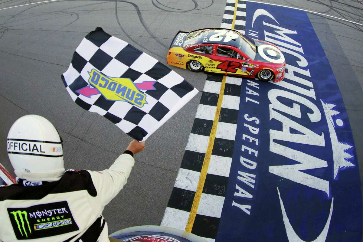 Kyle Larson takes the checkered flag to win the FireKeepers Casino 400 at Michigan International Speedway on Sunday.