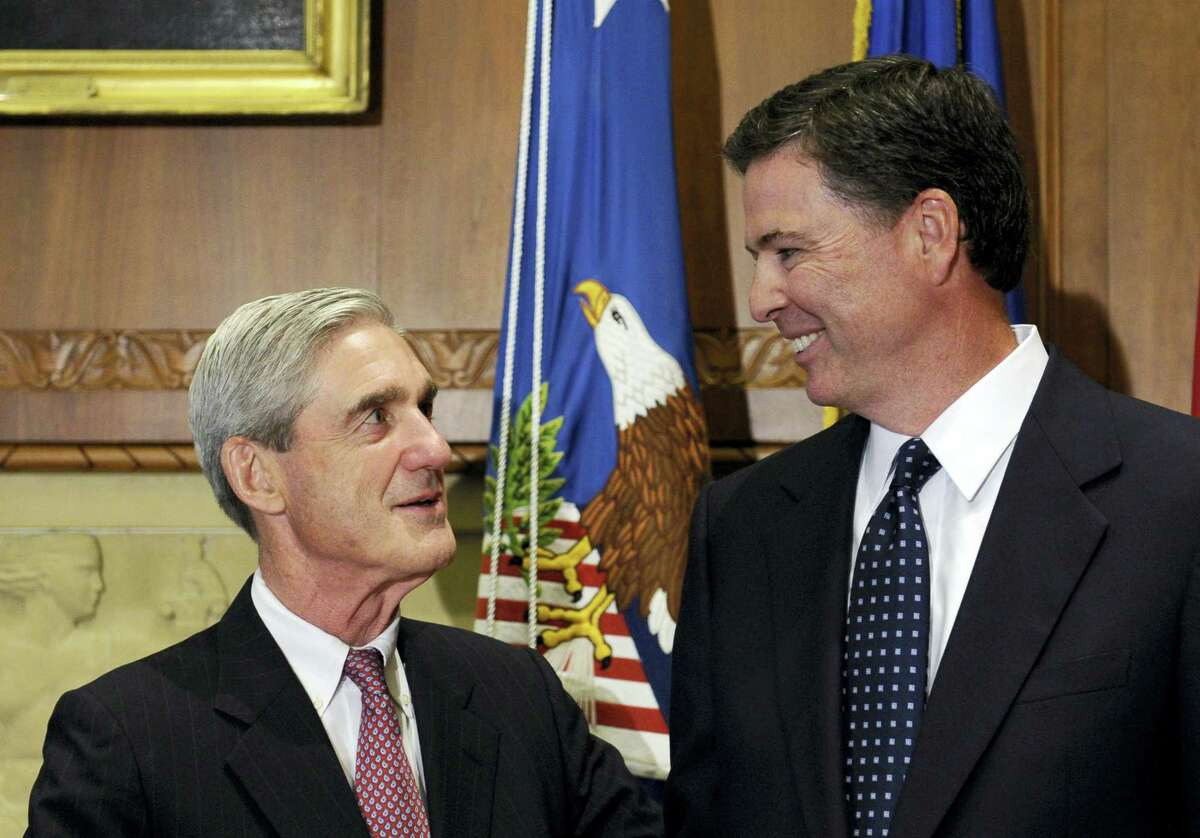 In this Sept. 4, 2013, file photo, then-incoming FBI Director James Comey talks with outgoing FBI Director Robert Mueller before Comey was officially sworn in at the Justice Department in Washington. On May 17, 2017, the Justice Department said is appointing Mueller as special counsel to oversee investigation into Russian interference in the 2016 presidential election.