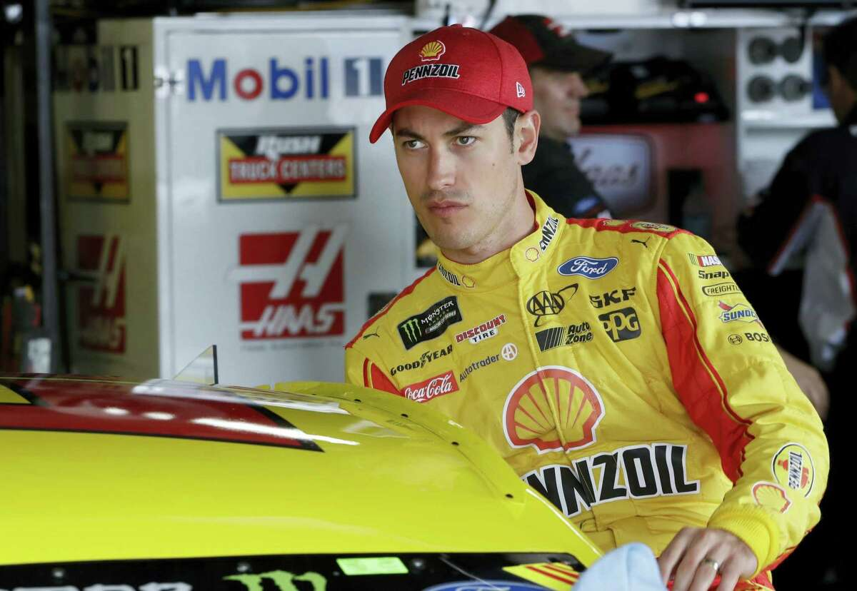 Joey Logano enters his car before a practice session.