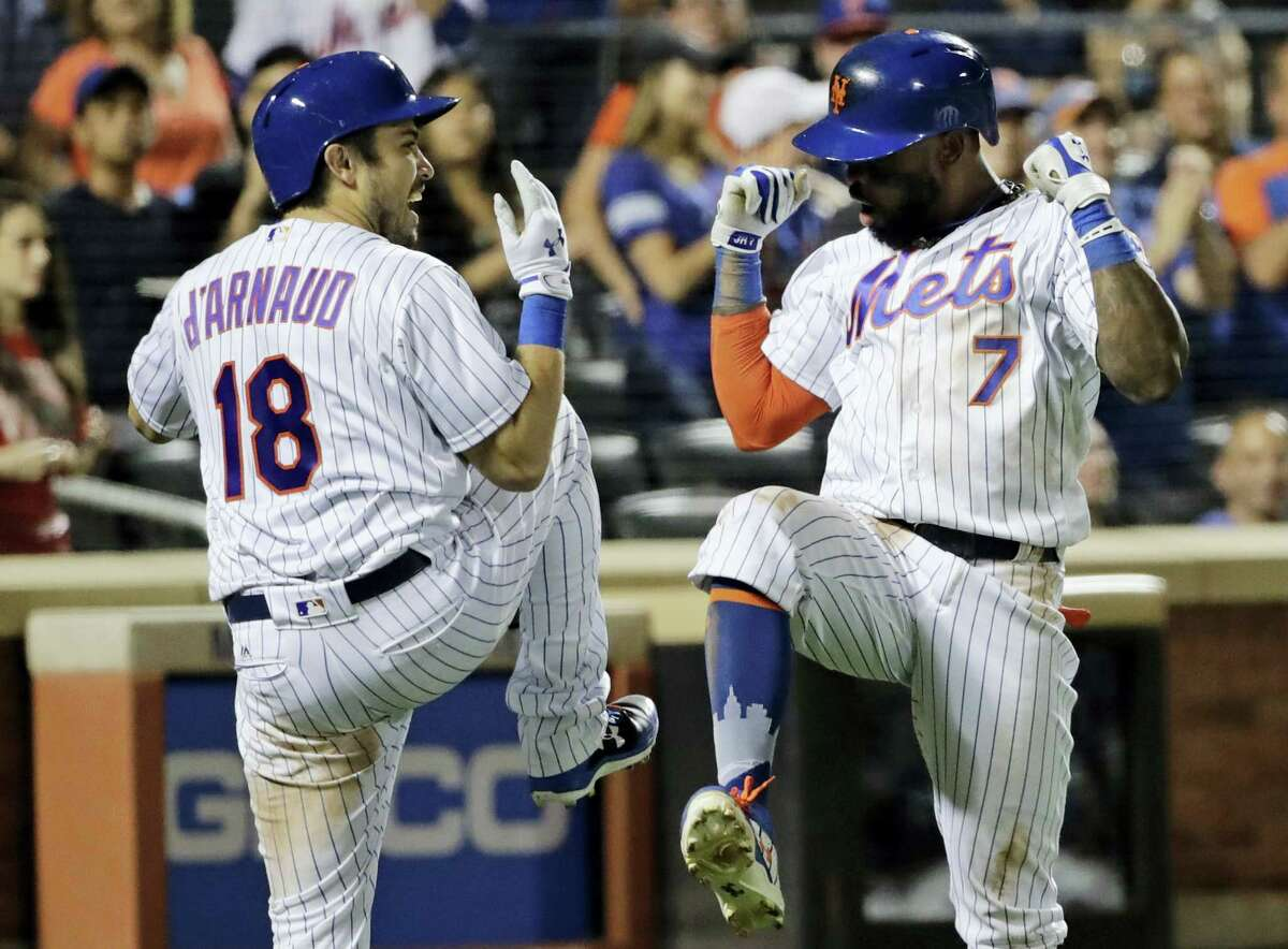 The Mets' Travis d'Arnaud, left, celebrates with Jose Reyes after Reyes hit a home run in the eighth inning Saturday in New York.