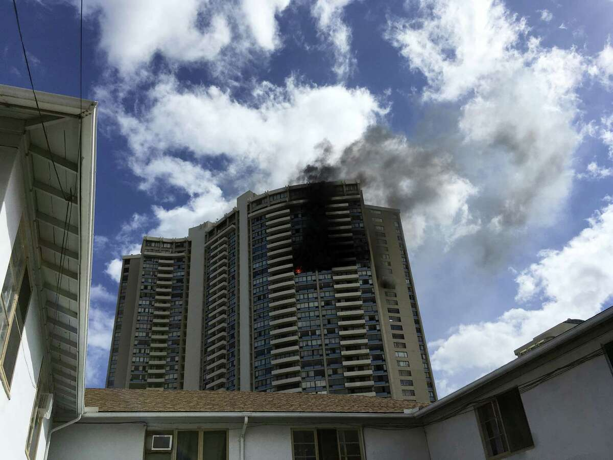 Smoke billows from a high-rise apartment building in Honolulu, Friday, July 14, 2017. Dozens of firefighters are battling the multiple-alarm fire at Marco Polo apartments that Honolulu Fire Department spokesman Capt. David Jenkins said started on the 26th floor and has spread to other units.