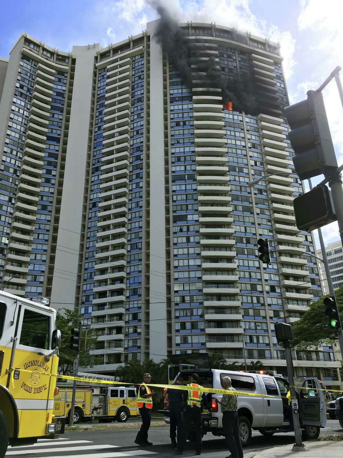 Law enforcement officers stand at the scene of a multi-alarm fire at a high-rise apartment building in Honolulu, Friday, July 14, 2017. Dozens of firefighters are battling the fire at Marco Polo apartments that Honolulu Fire Department spokesman Capt. David Jenkins said started on the 26th floor and has spread to other units.