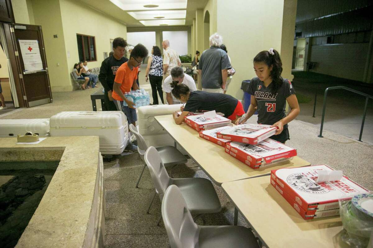 Volunteers prepare food and drinks at a school for the residents of the Marco Polo building, Friday, July 14, 2017, in Honolulu. A deadly fire broke out in the building killing three people and sent hundreds to a nearby school for the night.