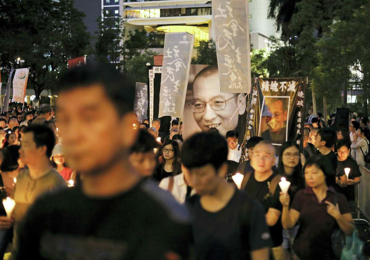 Protesters carry photos of late Chinese Nobel Peace laureate Liu Xiaobo as they march on a street to mourn him in Hong Kong, Saturday, July 15, 2017. China cremated the body of the imprisoned Nobel Peace Prize laureate who died earlier in the week after a battle with cancer amid international criticism of Beijing for not letting him travel abroad as he had wished.