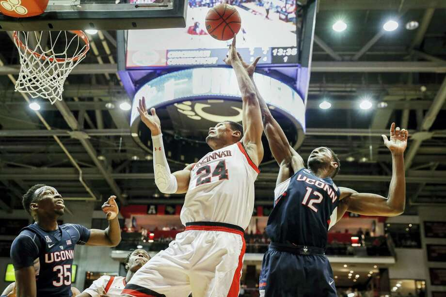 Cincinnati's Kyle Washington (24) shoots against UConn's Kentan Facey (12) during the first half of Cincinnati's 82-68 win Saturday. The Huskies host South Florida on Wednesday at Gampel Pavilion. Photo: JOHN MINCHILLO — THE ASSOCIATED PRESS  / AP