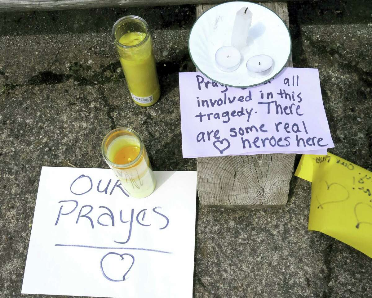 Well-wishing messages and candles for an injured employee are shown outside a grocery store in Estacada, Ore., Monday, May 15, 2017. Police say a man carrying what appeared to be a human head stabbed an employee at the grocery store.