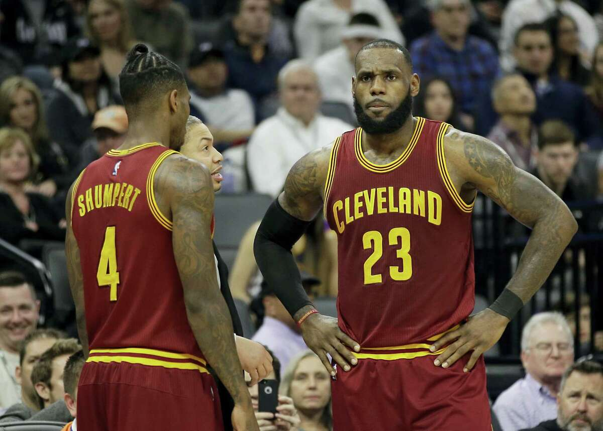 Cleveland Cavaliers head coach Tyronn Lue, center, talks with LeBron James, right, as Iman Shumpert, left, looks on during the second half of an NBA basketball game against the Sacramento Kings on Jan. 13, 2017 in Sacramento, Calif. The Cavaliers won 120-108.
