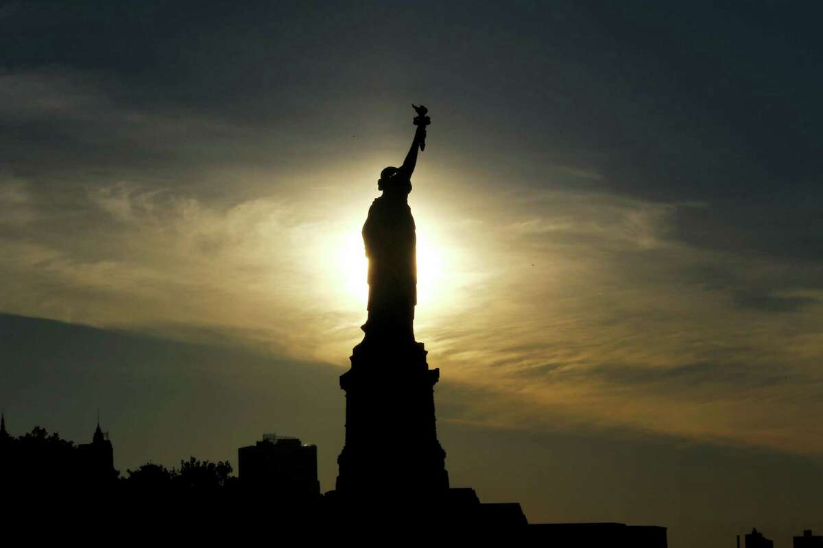 The sun rises behind the Statue of Liberty.