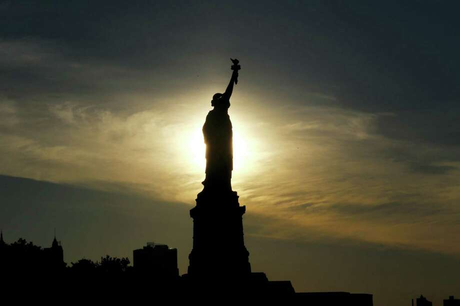 The sun rises behind the Statue of Liberty. Photo: File Photo  / Copyright 2016 The Associated Press. All rights reserved. This material may not be published, broadcast, rewritten or redistribu