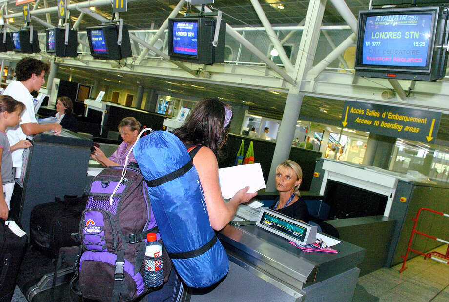 In this Aug. 11, 2006 file photo, passengers en route to London check in at Biarritz airport, southwestern France, The U.S. is expected to broaden its ban on in-flight laptops and tablets to include planes from the European Union, a move that would create logistical chaos on the world's busiest corridor of air travel. Alarmed at the proposal, which airline officials say is merely a matter of timing, European governments held urgent talks Friday, May 12, 2017,  with the U.S. Department of Homeland Security. Photo: Bob Edme — AP Photo File  / Copyright 2017 The Associated Press. All rights reserved.