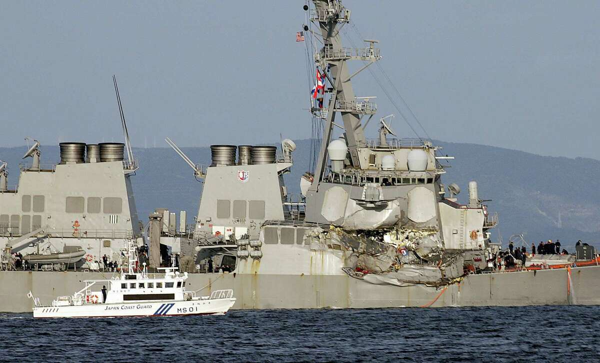 A Japan Coast Guard baot goes along with the damaged USS Fitzgerald near the U.S. Naval base in Yokosuka, southwest of Tokyo, after the U.S. destroyer collided with the Philippine-registered container ship ACX Crystal in the waters off the Izu Peninsula Saturday, June 17, 2017. Crew members from the destroyer USS Dewey were helping stabilize the damaged USS Fitzgerald after its collision off the coast of Japan before dawn Saturday, leaving seven sailors missing and at least three injured.