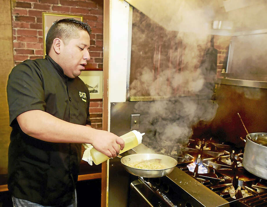 Chef Eduardo Saldana Pena, co-owner of Basta Trattoria (1006 Chapel St., New Haven), prepares branzino Amalfi, a pan-seared mild white fish with extra virgin olive oil, lemon and roasted garlic over truffled organic white beans and roasted zucchini. Photo: Peter Hvizdak — Register  / ©2017 Peter Hvizdak