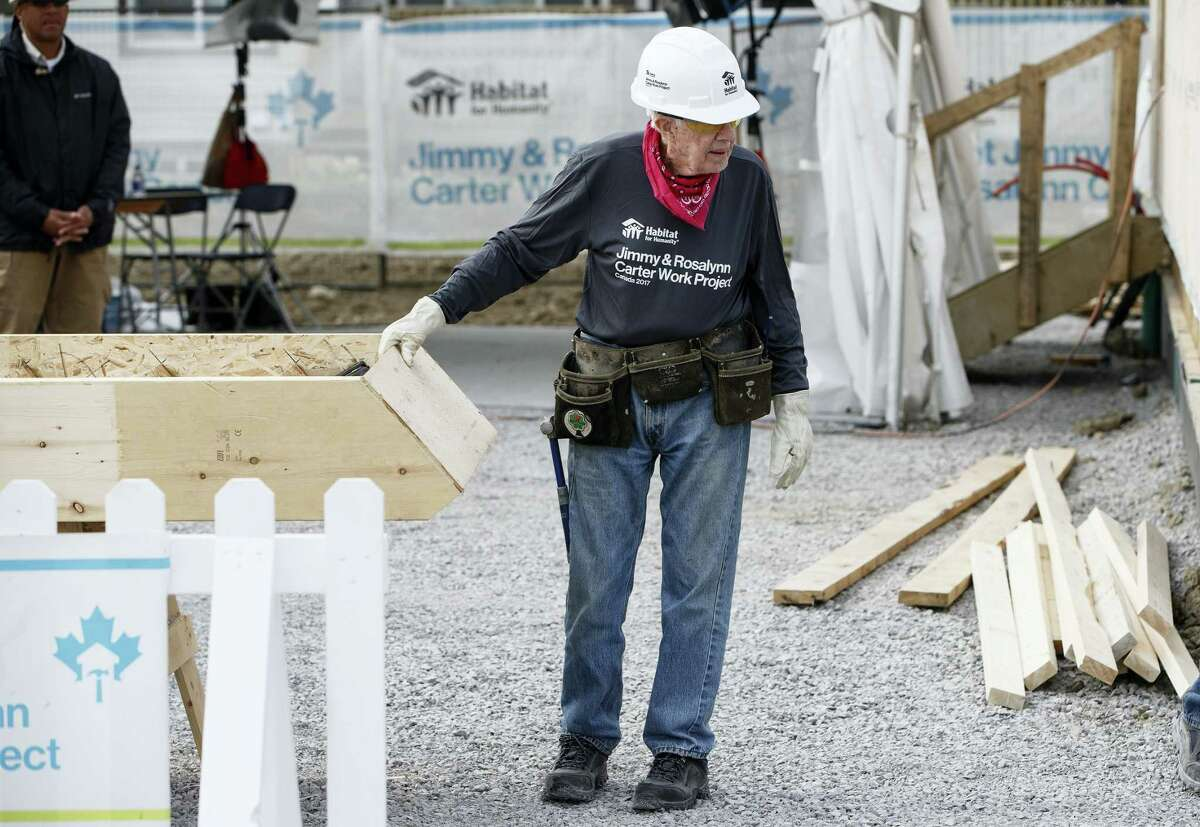 In this Tuesday, July 11, 2017, photo, former President Jimmy Carter helps build homes for Habitat for Humanity in Edmonton Alberta. Carter was back at a Habitat for Humanity worksite Friday, July 14, 2017, a day after he was hospitalized for dehydration while working with the organization to build homes for needy families in Canada.