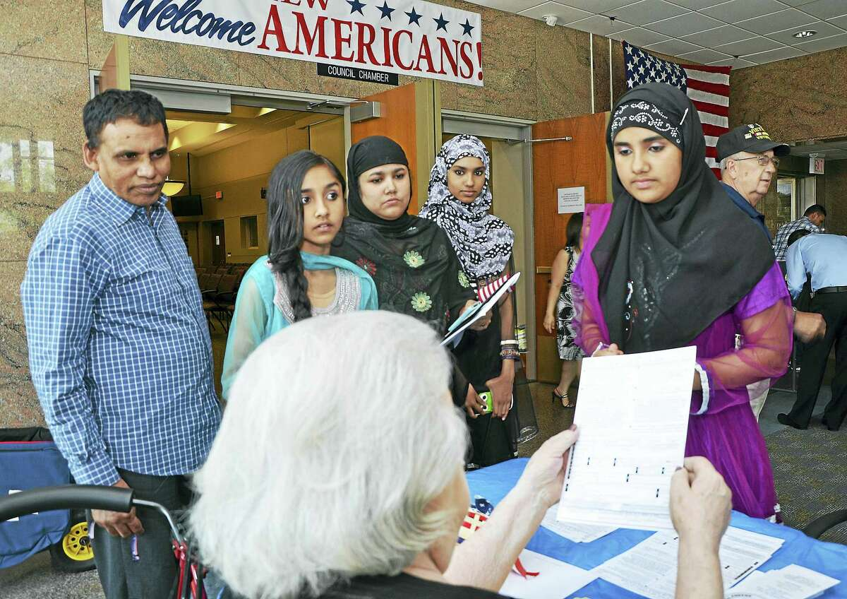 New citizens register to vote following the city's annual naturalization ceremony at Middletown City Hall in this file photograph. Mayor Dan Drew declared the city a safe haven for immigrants last week, saying local law enforcement will not do the U.S. government's job by enforcing federal immigration laws following President Donald J. Trump's executive order of Jan. 27.