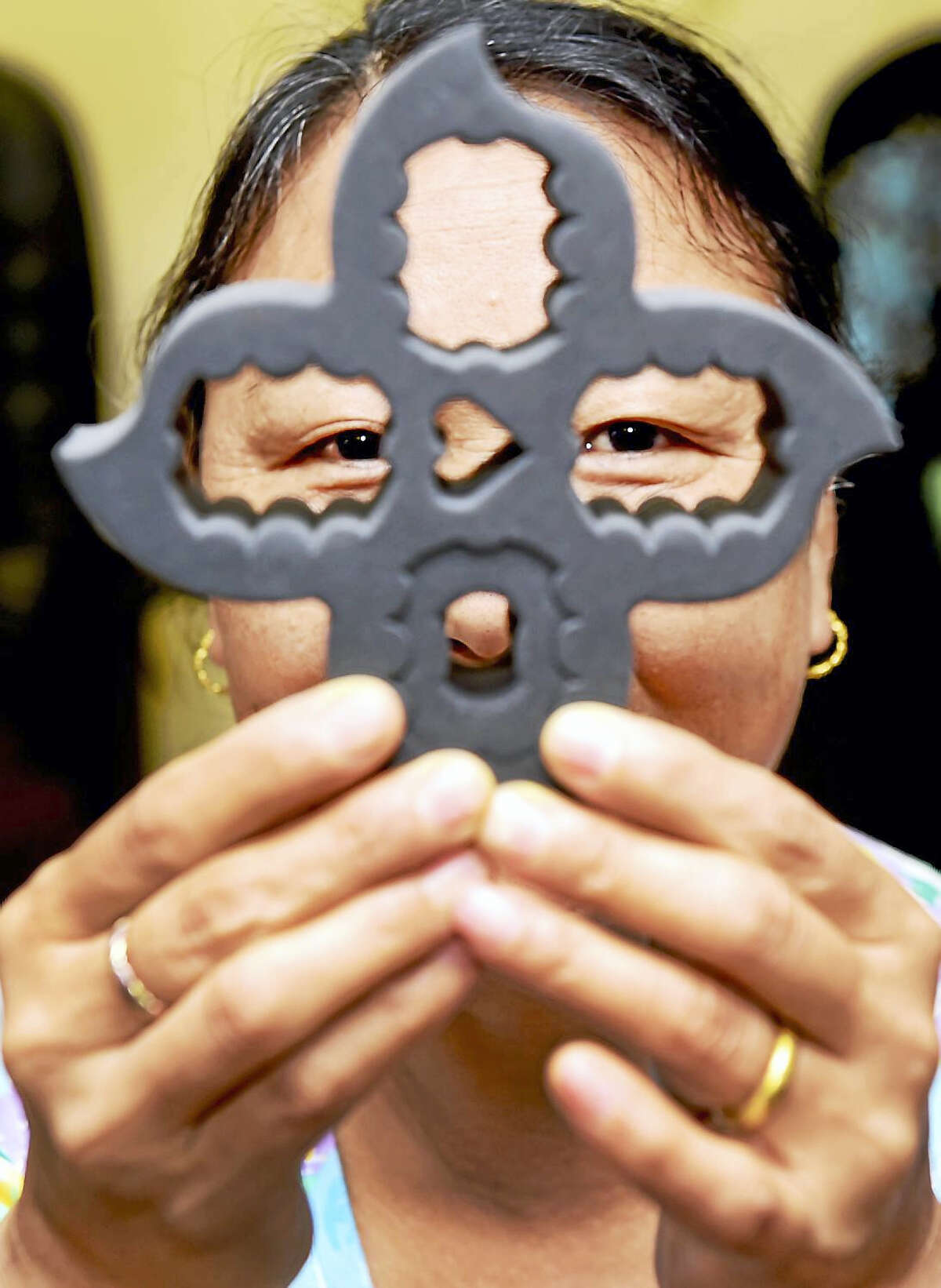 (Peter Hvizdak - New Haven Register) Kunga Choekyi, owner of K.C.'s Nails L.L.C. of Old Saybrook, a manicure and pedicure nail salon, with her patented invention, a nail polish holder called the Polish Posy, in the design of a lotus flower. The Polish Posy enables anyone to safely hold, tilt, and transport the bottles. Cyoekyi is a Tibetan and a follower of the Dalai Lama. A portion of the proceeds of the Polish Posy will go to organizations that care for Tibetan refugee children in southern India and to local charities.