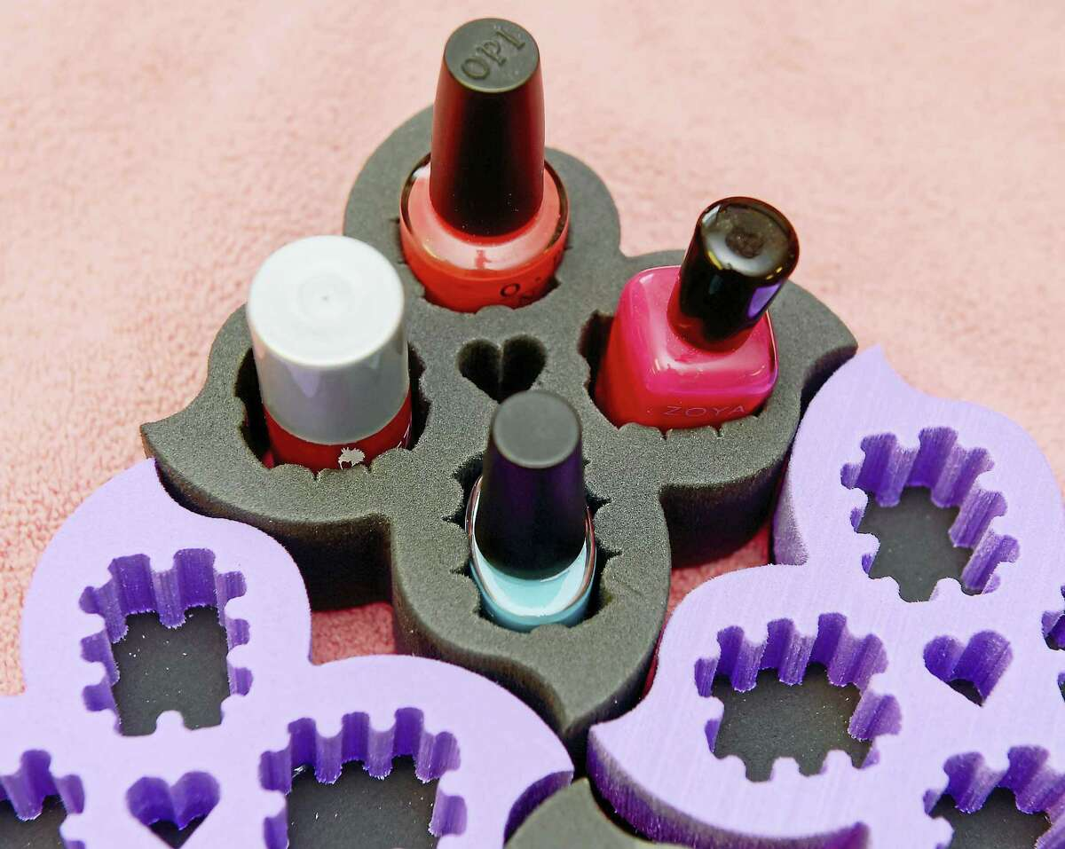 (Peter Hvizdak - New Haven Register)Kunga Choekyi, owner of K.C.'s Nails L.L.C. of Old Saybrook, a manicure and pedicure nail salon, invented a nail polish holder called the Polish Posy, in the design of a lotus flower. The patented Polish Posy enables anyone to safely hold, tilt, and transport the bottles. Cyoekyi is a Tibetan and a follower of the Dalai Lama. A portion of the proceeds of the Polish Posy will go to organizations that care for Tibetan refugee children in southern India and to local charities.